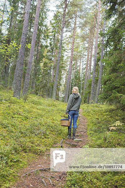 Schweden  Ostergotland  Finspang  Reife Frau beim Erkunden des Waldes