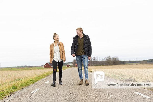 Schweden  Ostergotland  Mjolby  Teenagermädchen (14-15) und junger Mann auf der Landstraße