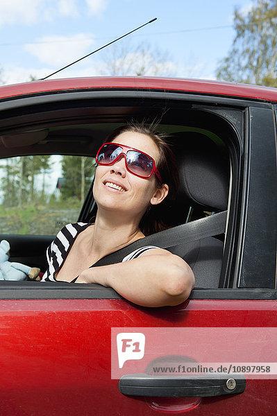 Schweden  Ostergotland  Vikbolandet  Mid-adult woman driving car  Blick nach oben