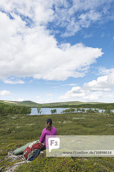 Sweden  Harjedalen  Ojon  Woman with backpack sitting on rock and looking at lake