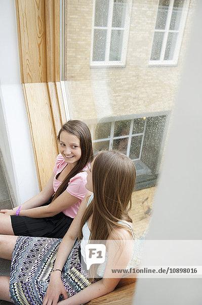 Schweden  Teenagermädchen (14-15) im Gespräch auf der Fensterbank