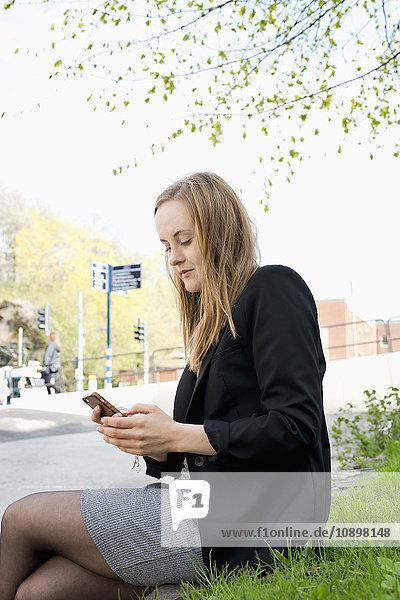 Schweden  Vastergotland  Göteborg  Junge Frau beim SMSen im Park
