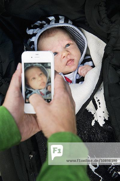 Schweden  Frau beim Fotografieren des neugeborenen Mädchens (0-1 Monate)