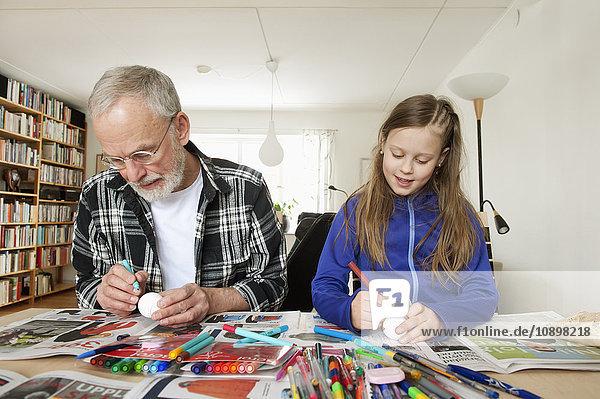 Schweden  Mädchen (10-11) mit Großvater beim Eierfärben im Wohnzimmer