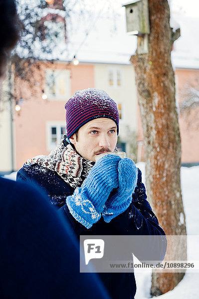Schweden  Stockholm  Mann trinkt im Winter heiße Schokolade im Freien