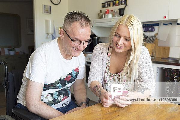 Schweden  Mann im Rollstuhl mit persönlicher Assistentin