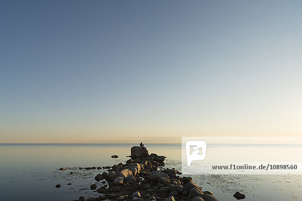 Schweden  Oland  Mann steht auf dem Kalmarsund und schaut auf die Aussicht