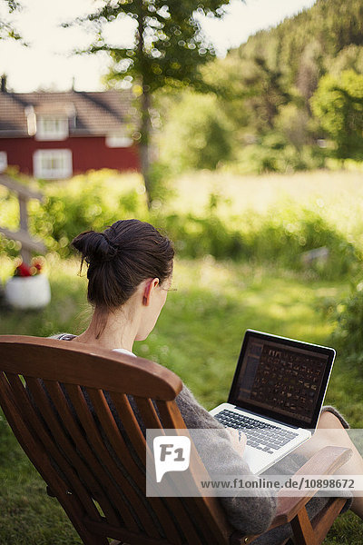 Schweden  Halsingland  Jarvso  Frau mit Laptop im Garten