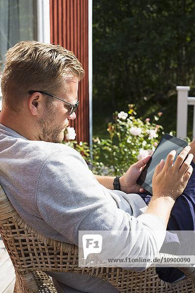 Sweden  Stockholm Archipelago  Grasko  Man using digital tablet outdoors