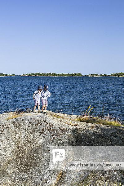 Sweden  Stockholm Archipelago  Grasko  Boys (4-5  6-7) on rock in bay