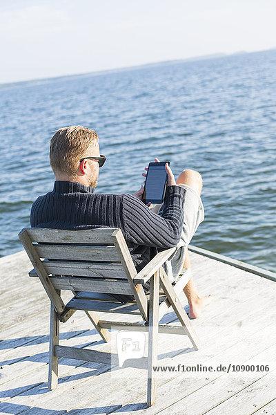 Sweden  Stockholm Archipelago  Grasko  Man sitting with tablet on jetty