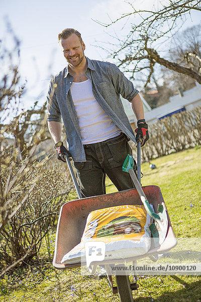 Sweden  Stockholm  Alvsjo  Man working in garden