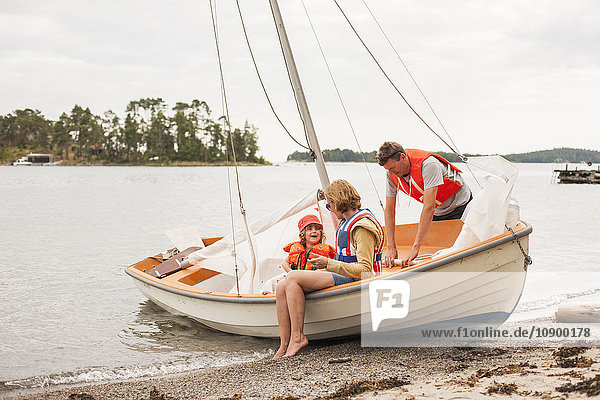 Sweden  Sodermanland  Stockholm archipelago  Musko  Family with child (4-5) wearing life jackets on sailboat