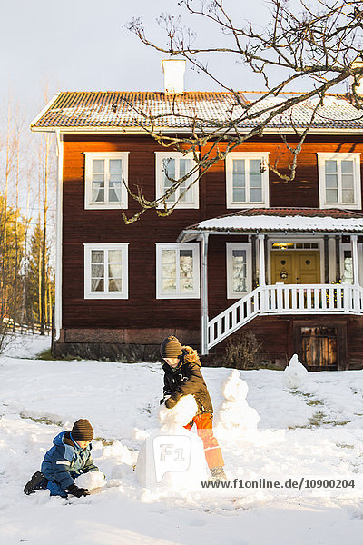 USA  Dalarna  Jarvso  Children (4-5  6-7) playing with snowman in front of house