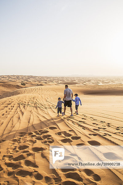 United Arab Emirates  Dubai  Father with sons (6-7  8-9) walking in desert