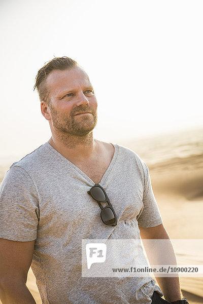 United Arab Emirates  Dubai  Mature man in desert at sunset