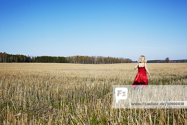 Schweden  Vastra Gotaland  Gullspang  Mädchen (4-5) im roten Kleid auf dem Feld