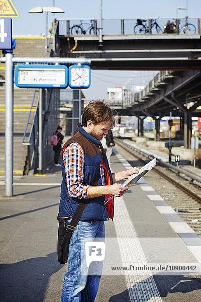 Deutschland  Berlin  Friedrichshain  Mann auf Karte am Bahnhof