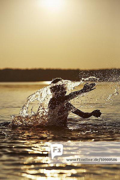 Schweden  Vastra Gotaland  Skagern  Junge (10-11) bei Sonnenuntergang im See planschend