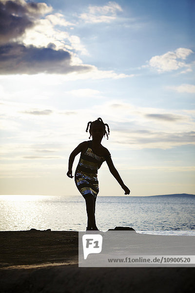 Kroatien  Dalmatien  Silba  Silhouette des Mädchens (6-7) beim Spielen an der Meeresküste