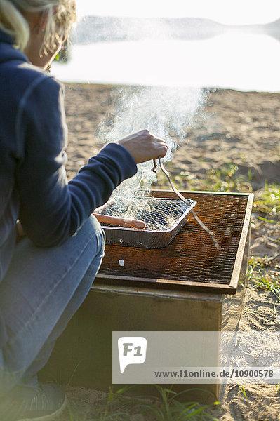 Schweden  Vastergotland  Lerum  Frau beim Kochen am See