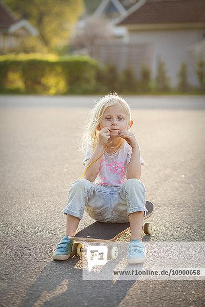 Schweden  Vastergotland  Lerum  Mädchenportrait (6-7) auf Skateboard