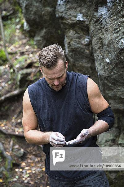 Sweden  Sodermanland  Tyreso  Sportsman with hands in chalk powder against rock