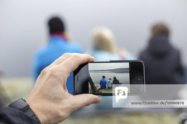 Schweden  Vastergotland  Lerum  Harskogen  Harsjon  Mann fotografiert Frau mit zwei Söhnen (10-11  12-13) mit Smartphone