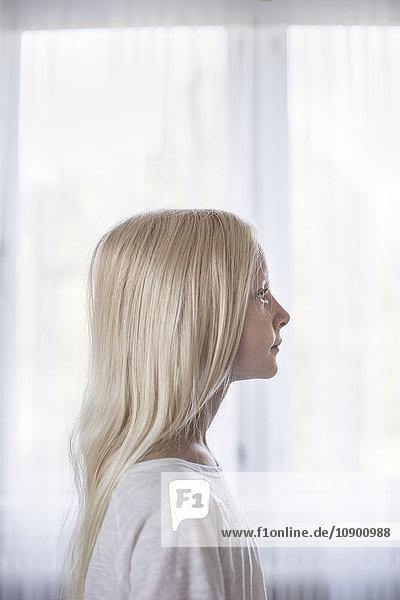 Schweden  Seitenansicht des blonden Mädchens (10-11) vor weißen Vorhängen