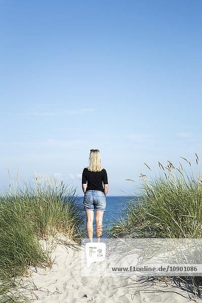 Schweden  Skane  Soderslatt  Beddinge  Rückansicht einer blonden Frau  die am Strand steht und auf das Meer blickt.