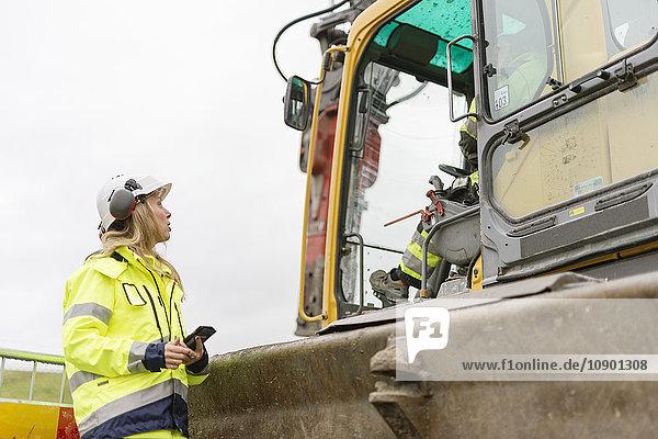 Schweden  Vastmanland  Frau im Gespräch mit dem Mann auf der Baustelle