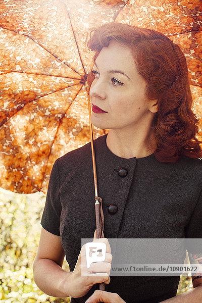 Schweden,  Rothaarige Frau mit Regenschirm