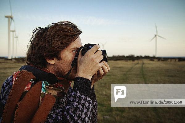 Sweden  Gotland  Nas socken  Young man photographing field