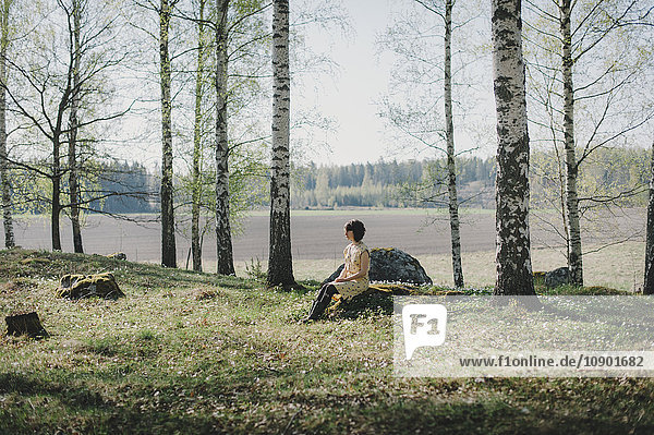 Sweden  Sodermanland  Vingaker  Attersta  Young woman sitting on stump in forest