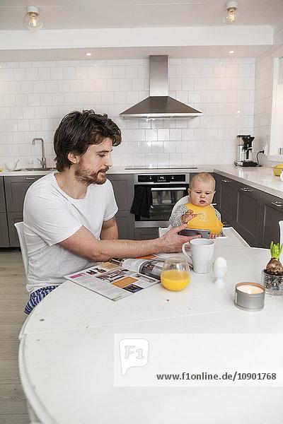 Schweden  Vater und Sohn (12-17 Monate) sitzend in der Küche