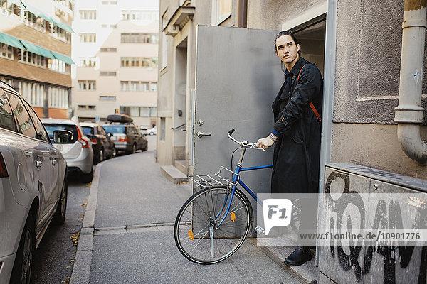 Schweden  Uppland  Stockholm  Vasastan  Junger Mann verlässt Haus mit Fahrrad