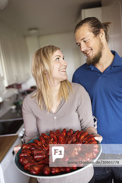 Sweden,  Man and woman holding crayfish on plate