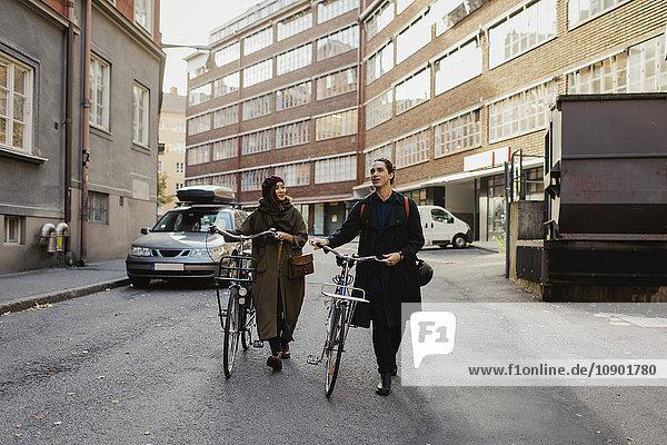 Schweden  Uppland  Stockholm  Vasastan  Zwei Personen  die mit dem Fahrrad durch die Straße laufen.