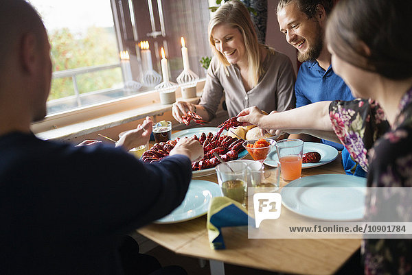 Sweden,  Three people sitting at table during crayfish party