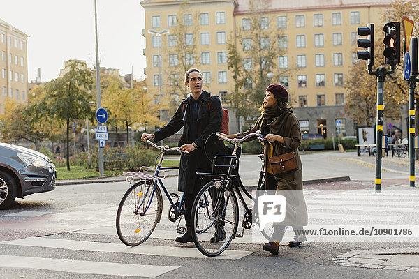 Schweden  Uppland  Stockholm  Vasastan  Vanadisplan  Zwei junge Leute mit Fahrrädern  die durch den Zebrastreifen laufen.