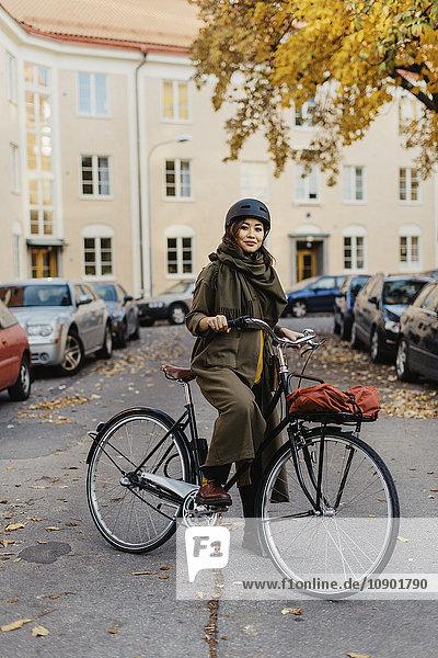 Schweden  Uppland  Stockholm  Vasastan  Rodabergsbrinken  Junge Frau stehend mit Fahrrad