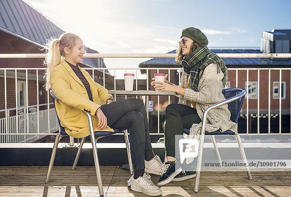 Schweden  Vasterbotten  Umea  Zwei junge Frauen sitzend  Kaffeetrinken
