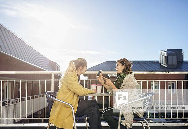 Schweden  Vasterbotten  Umea  Zwei junge Frauen am Telefon