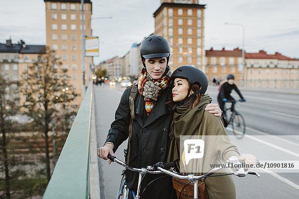 Schweden  Uppland  Stockholm  Vasatan  Sankt Eriksgatan  Junges Paar mit Fahrrädern auf der Straße
