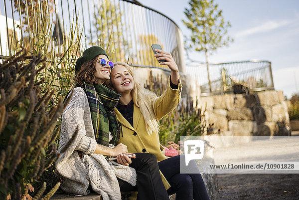 Schweden  Vasterbotten  Umea  Zwei junge Frauen  die Selfie nehmen