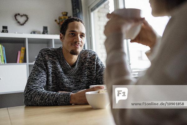 Schweden  Junges Paar am Tisch sitzend und Kaffee trinkend