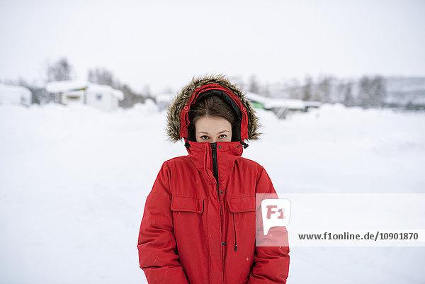 Schweden  Lappland  Hemavan  Portrait einer jungen Frau mit rotem Parka im Winter