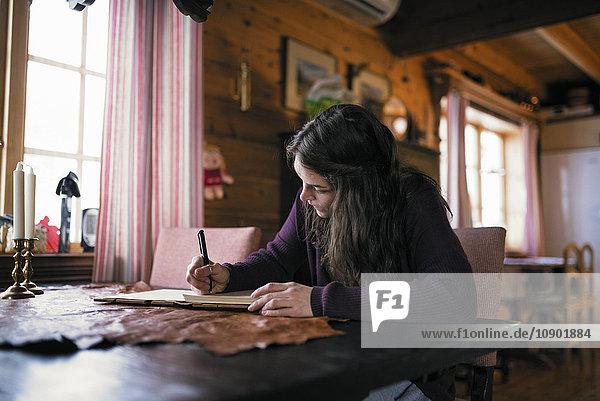 Schweden  Junge Frau am Tisch sitzend und schreibend in der Molkerei