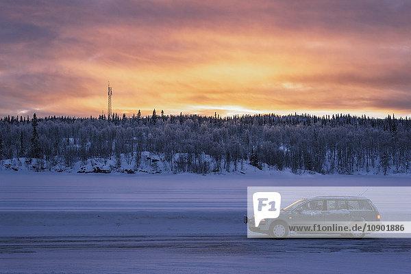 Schweden  Lappland  Hemavan  Auto auf schneebedeckter Piste bei Sonnenuntergang