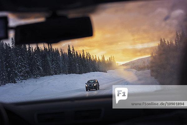 Schweden  Lappland  Hemavan  Auto durch die Windschutzscheibe gesehen  mit Schnee bedeckter Feldweg bei Sonnenuntergang.